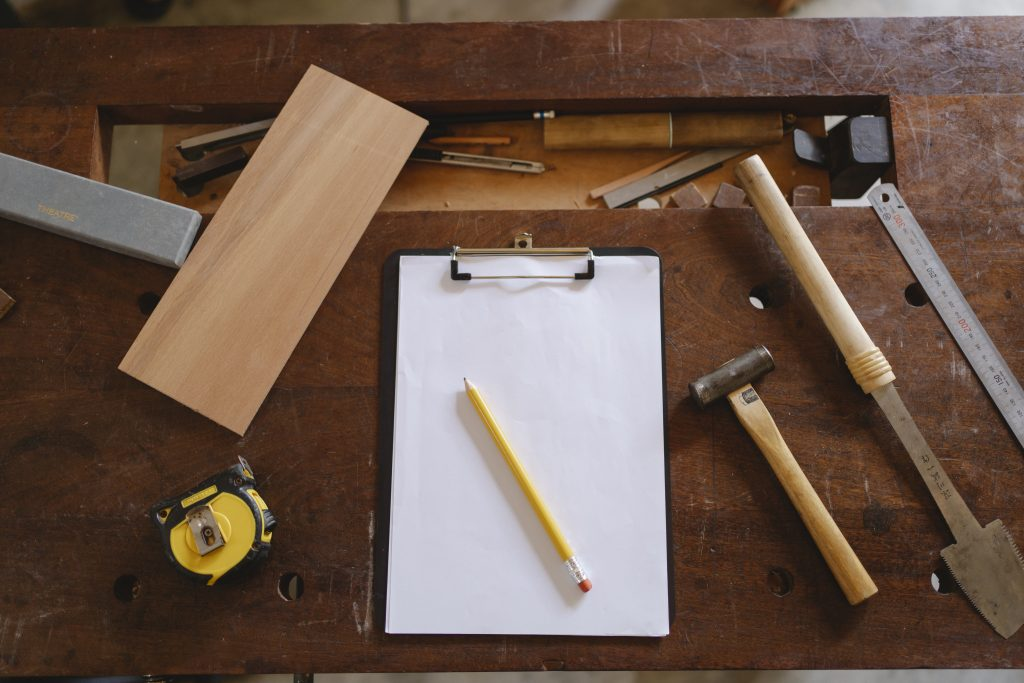 Yellow pencil on white paper and carpentry tools